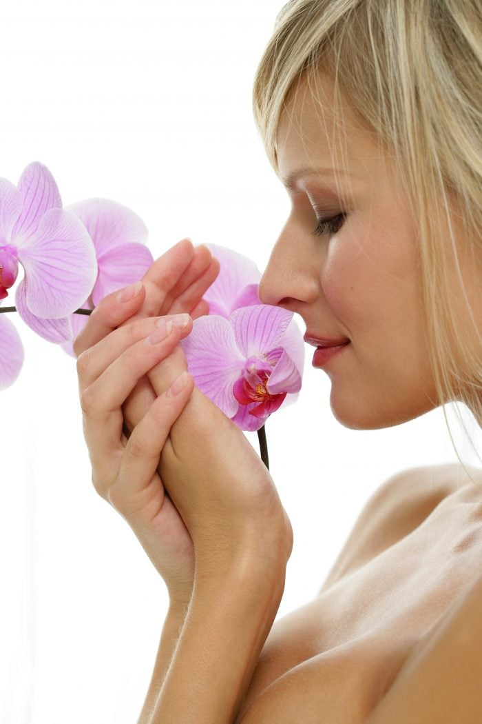 Woman smelling flowers at medspa in OKC