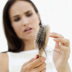 woman distraught at hair loss shown in brush.